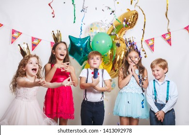 Group of kids throwing colorful confetti and looking happy on birthday party
