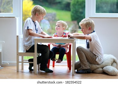 Group of kids, two twin brothers with little toddler sister playing indoors making paper planes sitting nearby big window with street view on a sunny summer day