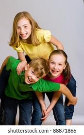 A group of kids wearing colorful shirts having fun.