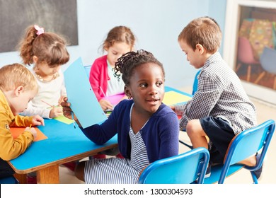 Group of kids while painting together in the drawing class in kindergarten or preschool