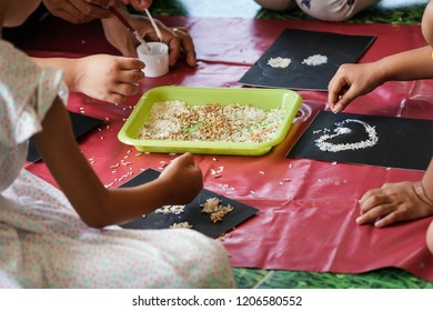 Group of kids work in the art of grain , rice seeds.