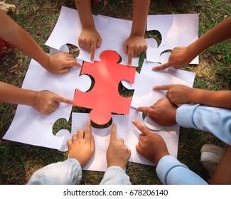Group kids/children hands holding jigsaw/ puzzles pieces on grass/red piece center.concept: cooperation, teamwork, learning, activity, business, working, helping, diverse, education, school, playing.