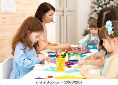 Group of kindergarten children at daycare. Preschool children working with color paper, sciccors and glue on art class in classroom