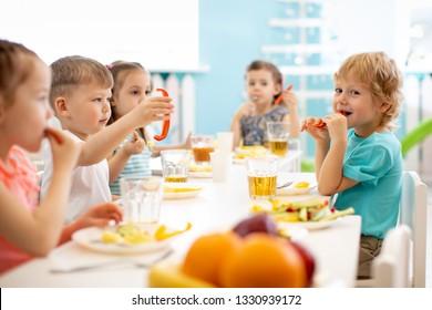 Group of kindergarten kids eating healthy food lunch break together