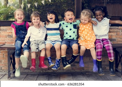 Group of kindergarten kids friends arm around sitting and smiling fun - Shutterstock ID 636281354