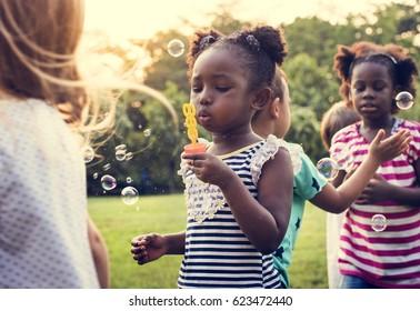 Group of kindergarten kids friends playing blowing bubbles fun