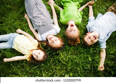 A group of kindergartners lies on the grass in the park smiling.