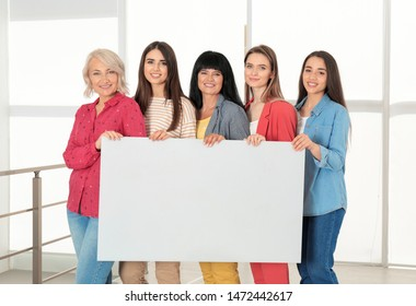 Group of ladies with empty poster near window indoors, space for text. Women power concept