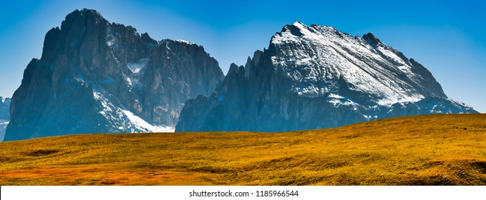 Group of Langkofel with first snow of season and orange hill in foreground in a clear day and blue sky, South Tyrol - Italy
