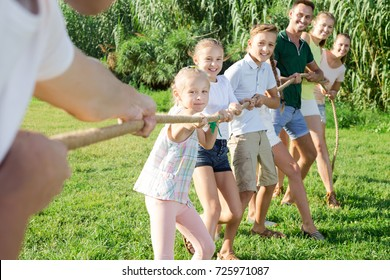 Group of laughing adult people with happy little kids having fun together outdoors pulling rope