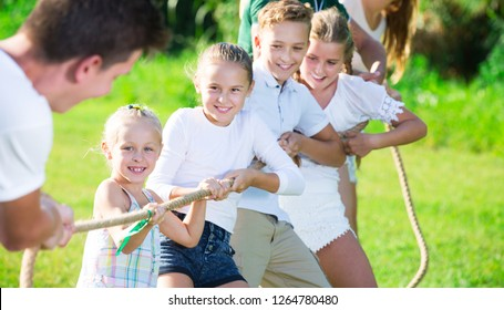 Group of laughing adult people with kids having fun together outdoors pulling rope