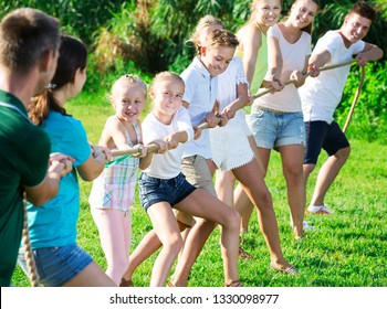Group of laughing adult people with little kids having fun together outdoors pulling rope