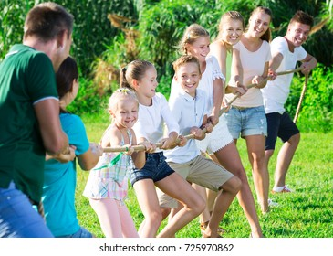 Group of laughing adult people with smiling kids having fun together outdoors pulling rope