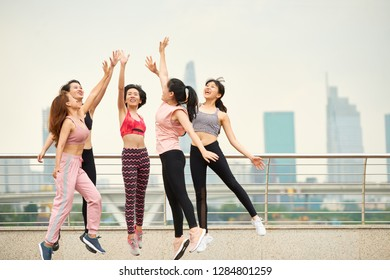 Group of laughing Asian woman in sportswear jumping and giving high five against cityscape