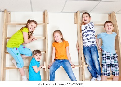 Group of laughing basic school students sitting on wall bars