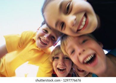 Group of laughing children having fun outdoors smiling at camera