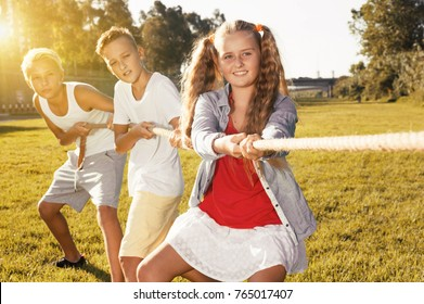 Group of laughing children having fun together outdoors pulling rope