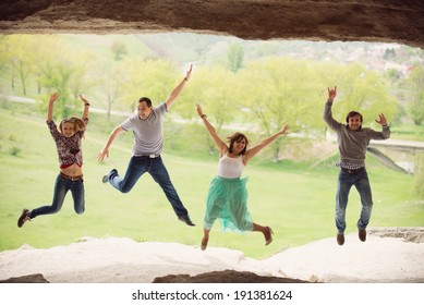 group of laughing friends jump in cave