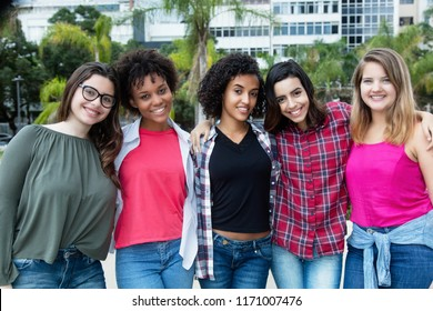 Group of laughing latin american and african and arabic girls outdoors in the summer in city