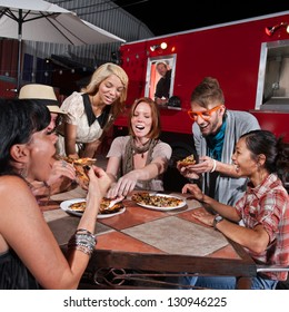 Group of laughing people eating pizza at a food truck