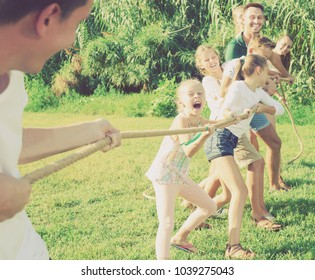 Group of laughing people with kids having fun together outdoors pulling rope