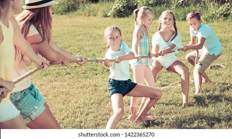 Group of laughing people with little kids having fun together outdoors pulling rope