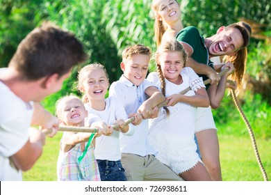 Group of laughing young people with kids having fun together outdoors pulling rope