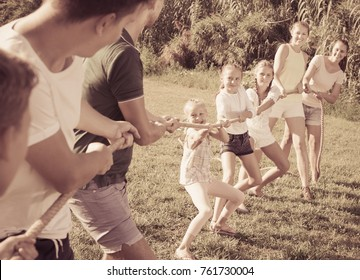 Group of laughing young people with little kids having fun together outdoors pulling rope