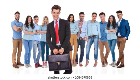 group leader standing while holding suitcase with both hands in front of his casual, happy team, on white background, full body