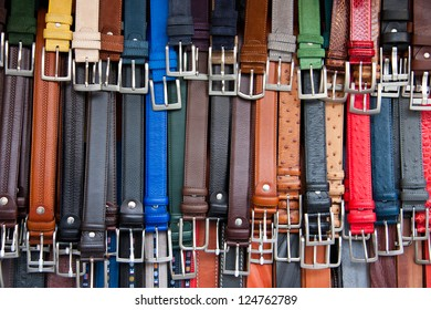 Group of leather belts on a street market in Florence.