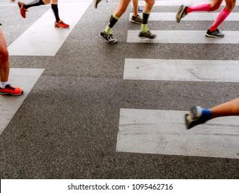 group legs runners athletes running street crosswalk