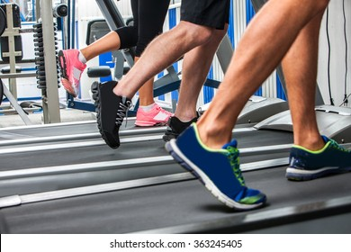 Group of legs wearing sneakers running on treadmill.