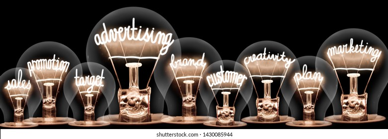 Group of light bulbs with shining fibers in a shape of Advertising, Marketing, Sales and Customer concept related words isolated on black background; horizontal composition