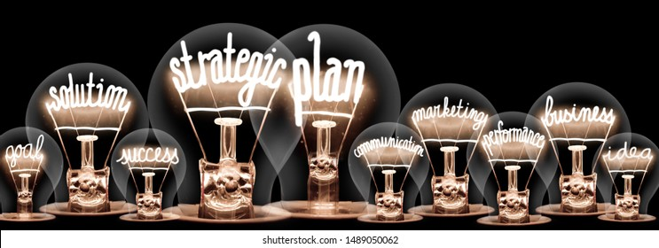 Group of light bulbs with shining fibers in a shape of Strategic Plan, Solution, Success and Idea concept related words isolated on black background