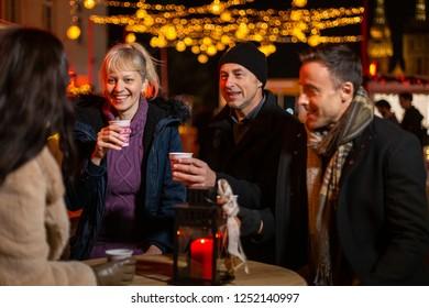 Group listening friend cheering at Christmas market, Zagreb, Croatia.
