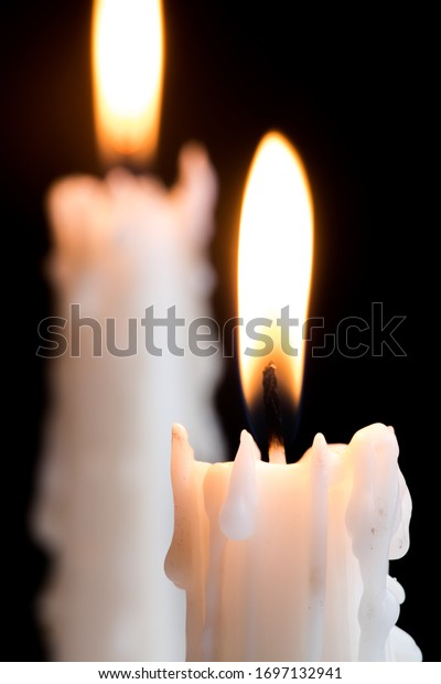 Group of lit candles.  White candles burning against a dark background