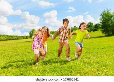 Group of little 6 and 7 years old kids, boys and girls running holding hands together in the park