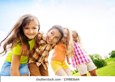 Group of little 6 and 7 years old smiling kids smiling standing outside in the park