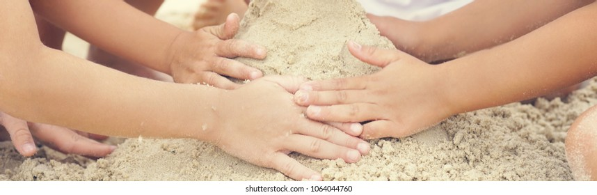 Group of little children build a sand tower, hands closeup