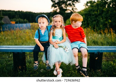 Group of little emotional kids sitting on bench outdoor in countryside. Girl in dress between two guys. Difficult relations. Youth jealousy. Funny loving triangle. Joy, sorrow, hurt and offense