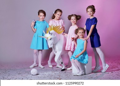 Group little girl in beautiful pink,blue dresses next with unicorn figure. Five lady children together,clothes,catalog fashion collection.Cheerful girlfriends,studio,pastel background.Models 5 kids.