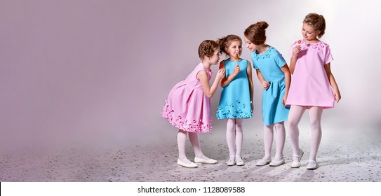Group little girl in beautiful pink,blue dresses.Four children advertise clothes for clothing catalog.Studio,pastel background banner,copy space for text,shop,advertising. Concept fashion models kids.