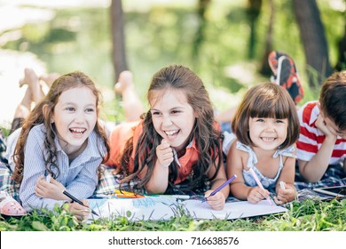 group of little girls and boy painting with paintbrush and colorful paints