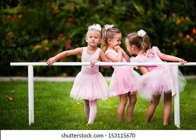 Group of little girls doing ballet bar exercises at beautiful summer garden background