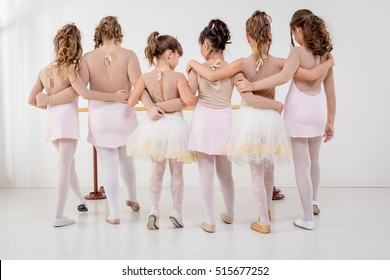 Group of a little girls in dresses during ballet class. Rear view.