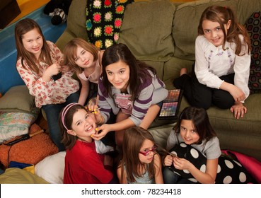 Group of little girls fixing hair and applying makeup