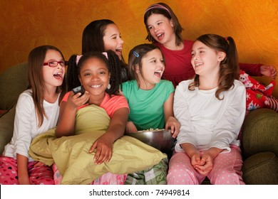Group of little girls watching television while eating popcorn