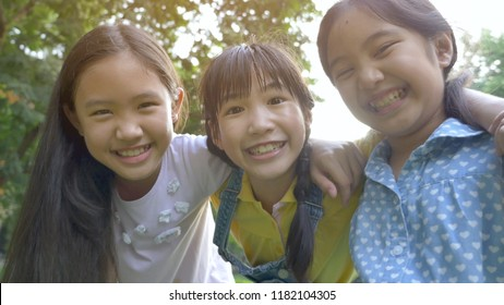Group of little happy Asian girls playing together in the park