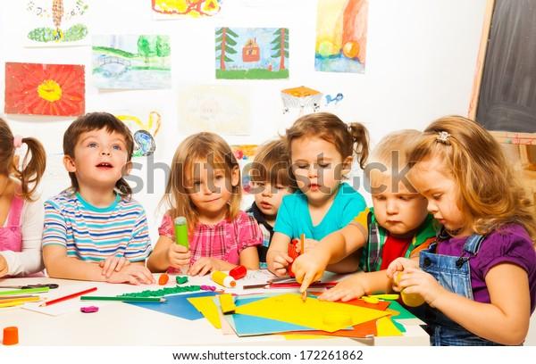 Gruppe kleiner Kinder, die mit Bleistiften malen und mit Leimklebstoff auf der Kunstklasse im Kindergarten kleben