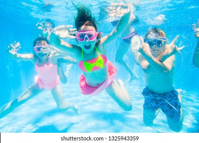 group of little kids swimming  in pool  underwater.